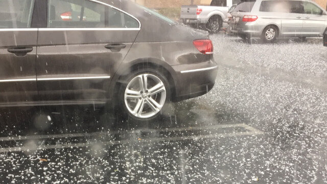 Hail storm damages vehicles in parking lot